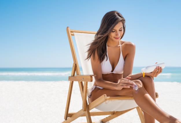 woman-applying-suntan-lotion_256588-704